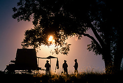 silhouette of three men preparing dinner under a tree on the trail