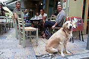 Men at a taverna with their golden retriever dog in Monastiraki. Athens is the capital and largest city of Greece. It dominates the Attica periphery and is one of the world's oldest cities, as its recorded history spans around 3,400 years. Classical Athens was a powerful city-state. A centre for the arts, learning and philosophy.