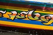 Longtail boat journey on Khlong Bangkok Yai canal, one of the canals which comes off Bangkok's Chao Phraya River. Painted motif on the side of the boat.