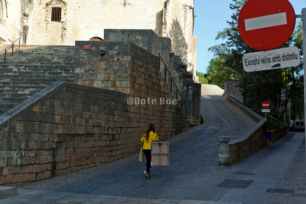 woman walking with painting canvas in Girona Spain