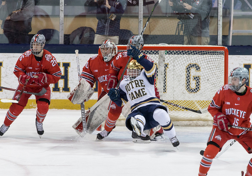 March 17, 2018:  Ohio State defenseman Matt Joyaux (46) and Notre Dame forward Dylan Malmquist (25) battle in the crease during NCAA Hockey game action between the Notre Dame Fighting Irish and the Ohio State Buckeyes at Compton Family Ice Arena in South Bend, Indiana.  Notre Dame defeated Ohio State 3-2 in overtime.  John Mersits/CSM