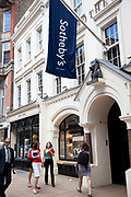 "Sotheby's auction house. Exclusive shops on New Bond Street, Mayfair, central London. It is one of the principal streets in the West End shopping district and is more upmarket. It has been a fashionable shopping street since the 18th century. Technically ""Bond Street"" does not exist: The southern section is known as Old Bond Street, and the northern section, which is rather more than half the total length, is known as New Bond Street. The rich and wealthy shop here mostly for high end fashion and jewellery."