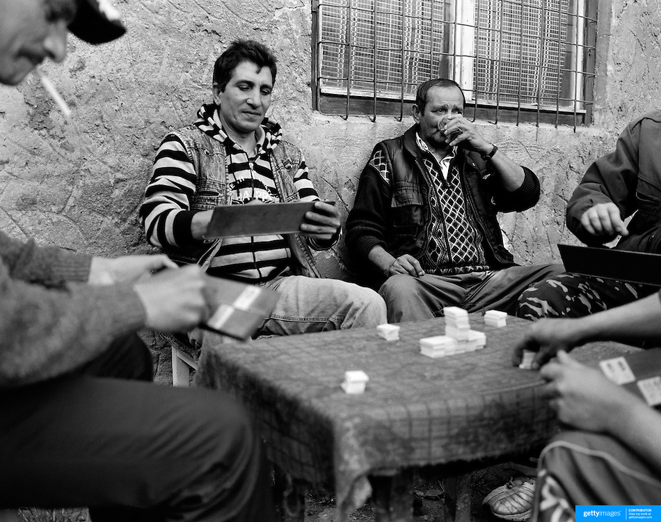 Men spend the afternoon playing a game for small wagers in a housing estate of the small Romanian town of Copsa Mica, Transylvania, Romania. Copsa Mica was once described as the most polluted town in Europe. May 9, 2008. Photo Tim Clayton. ..Copsa Mica, a small industrial town deep in Transylvania, Romania, was described during the 1990s as the most polluted town in Europe with lead levels reaching were more than 1000 times the allowable International limits and life expectancy nine years shorter than the National average...The pollution was caused entirely by two factories, Carbosin produced black for dies and tires and closed in 1993 while Sometra, a nonferrous smelter is still operational today...The pollution was so bad sheep were black, covered in soot and health officials advised against eating livestock or vegetables and drinking the water or milk...The Communist rule of Nicolae Ceausescu is blamed for the widespread environmental degradation that left industrial parts of Romania in ecological disaster. Industry was situated in a way to concentrate pollution in small areas leaving the rest of the country relatively free of pollution.Copsa Mica in particular was left an environmental disaster...The pollution caused a direct affect on human health with widespread Lung disease, Impotency, the highest infant mortality rate in Europe, Lead poisoning andbehavioral problems...Fifteen years on since the closure of Carbosin in 1993, the factory skeleton remains as part of the towns bleak landscape, Unfinished communist style housing blocks still stand in the heart of the towns housing estate. The town's inhabitants arestill trying to recover from the long lasting effects of pollution...Recent survey's found the soil contained so much lead that it was 92 times above the permitted level; the vegetation had a lead content 22 times above the permitted level. While toxins have penetrated at least one meter (three feet) into the soil leaving the entire
