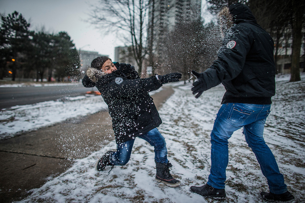 Syrian refugee Nasimi Batal Al Hasan plays with his brother Ali (right) in the snow outside of their apartment building in Mississauga, Ontario, Canada, Thursday January 21, 2016.   (Mark Blinch for the BBC)