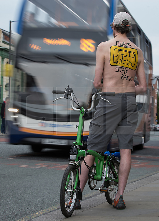 © Licensed to London News Pictures. 12/06/2015. Manchester, UK. A cyclist stands by fast-moving buses . Hundreds take part in the World Naked Bike Ride , which sees cyclists undress and cycle nude through Manchester City Centre . Photo credit: Joel Goodman/LNP