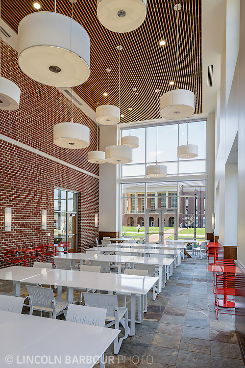 A cafe style interior at Liberty Student Center that is currently empty. Modern light fixtures hang from a very high ceiling over metal  tables and chairs.