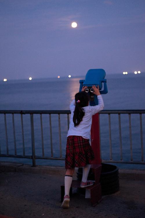 Korean girl looking through binoculars to the sea and full moon / Mangyang rest area, South Korea, Republic of Korea, KOR, 04 October 2009.