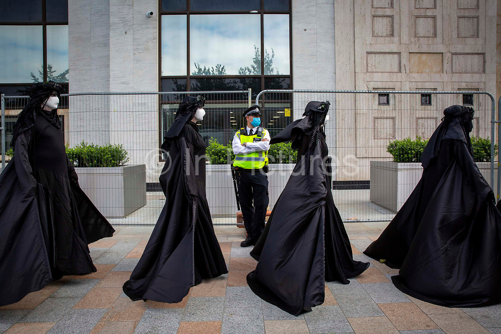 Police keep a close eye on Oil Slick, black rebels demonstrate as part of the Extinction Rebellion 'Shell Out' protest on 8th September 2020 in London, United Kingdom. The environmental group gathered outside the Shell building to protest at the ongoing extraction of fossil fuels and the resulting environmental record. Extinction Rebellion is a climate change group started in 2018 and has gained a huge following of people committed to peaceful protests. These protests are highlighting that the government is not doing enough to avoid catastrophic climate change and to demand the government take radical action to save the planet.