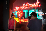 Model Charli is photographed by a photographer working on a fashion shoot in front of the neon Heartbreak Hotal sign. The South Bank is a significant arts and entertainment district, and home to an endless list of activities for Londoners, visitors and tourists alike.