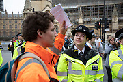 Climate change activist from the Extinction Rebellion group with letters to MPs and police lines at Parliament Square in protest that the government is not doing enough to avoid catastrophic climate change and to demand the government take radical action to save the planet, on 23rd April 2019 in London, England, United Kingdom. Extinction Rebellion is a climate change group started in 2018 and has gained a huge following of people committed to peaceful protests.