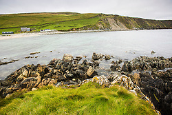 The Taing, a small grass covered tidal island on the beach at Norwick on the north east coast of Unst.   Although unremarkable, the island and its neighbouring rocks are of great interest to geologists because of their unusual geology.  Eastern Unst is an ophiolite.  This is where a section of the earth's crust from beneath the ocean collided with an ancient continent and was pushed up onto it 420 million years ago.  At Norwick beach immediately to the north of the Taing there is a shallow sand filled trench and you can see where the ophiolite and continent meet.  The island is comprised of serpentinite and talc steatite, while the rocks to the north are phyllite.