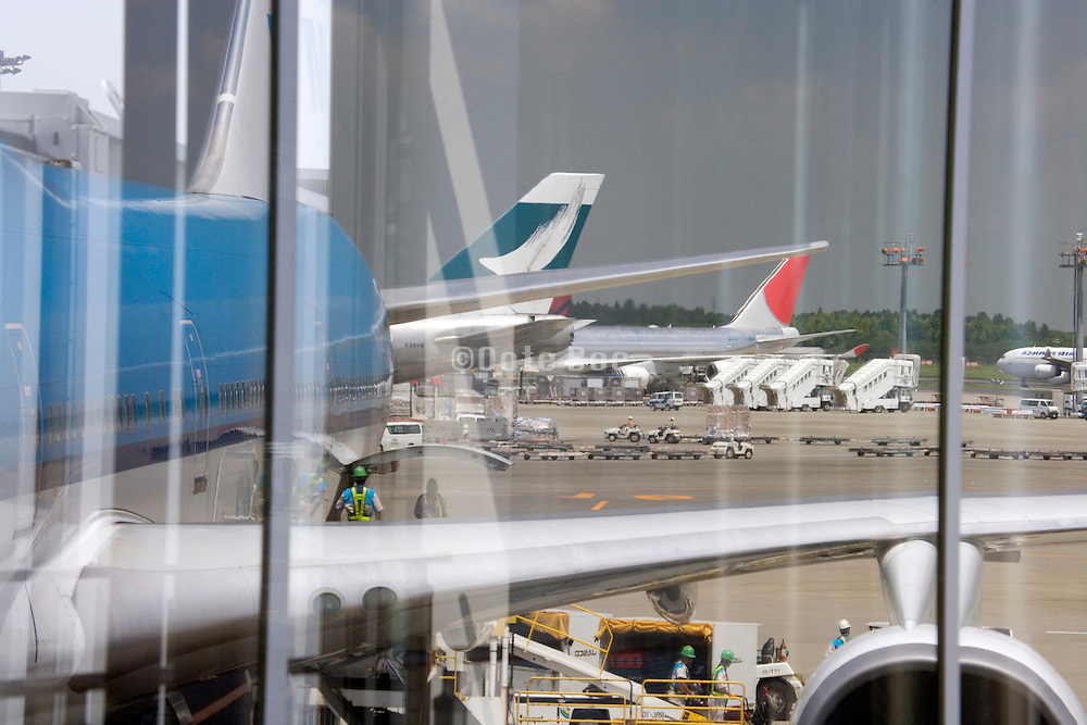 passenger Jumbo jets reflecting in window at Narita international airport Tokyo Japan
