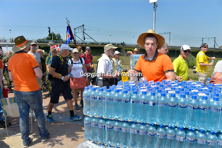 Nederland, the Netherlands, Nijmegen, 19-7-2016 1e dag voor de  lopers van de 100e 4 daagse. Via de Waalbrug ging het naar de Betuwe en via de Oosterhoutsedijk in een langgerekt lint weer terug. Extra waterpunten waren ingericht t langs het parcours. Hier worden flessen water uitgedeeldThe International Four Day Marches Nijmegen, or Vierdaagse, is the largest marching event in the world. It is organised every year in Nijmegen in mid-July as a means of promoting sport and exercise. Participants walk 30, 40 or 50 kilometers daily, and, on completion, receive a royally approved medal, Vierdaagsekruis. The participants are mostly civilians, but there are also a few thousand military participants. The vierdaagse, Dutch for Four day Event, is an annual walk that has taken place since 1909, being based at Nijmegen since 1916. Foto: Flip Franssen