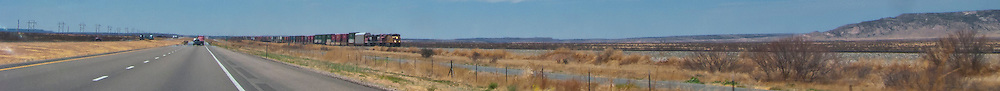 a freight train, Interstate 20, and a power line fill a panorama in rural eastern New Mexico, USA