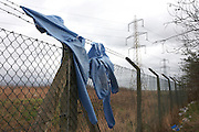 Tangled clothing hangs on barbed wire fencing below an enbankment alongside the A13 road in Dagenham, Essex..