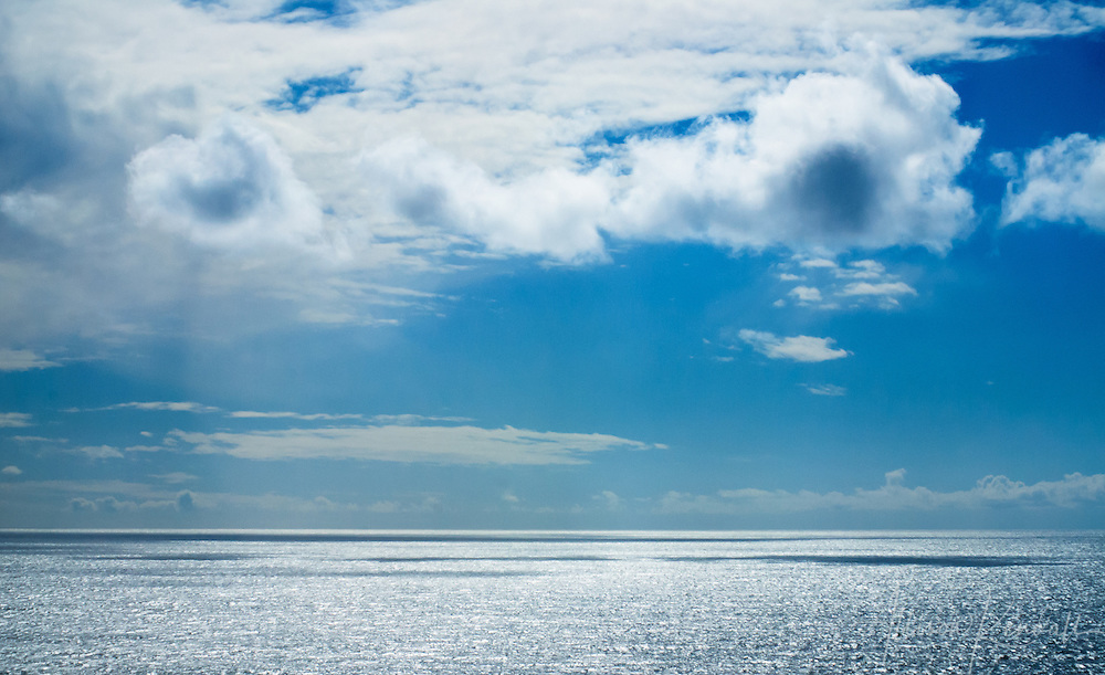 Brilliant blue sky, white clouds, and glittering sunlight on an endless ocean horizon off the coast of Big Sur, California