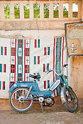 A moped leans on a shop in the streets of Segou, Mali