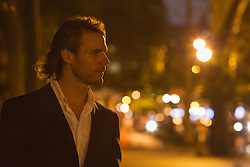 profile of a man in New York City on the street at night
