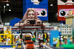 The SEC in Glasgow hosts Brick Live, the largest LEGO exhibition in the UK. Featuring models made up of over 6 million bricks, LEGO enthusiasts can build their own creations as well as admiring the models created by some of the leading designers including Scotland's Nick Clayton and Rocco Buttliere from Chicago.<br /> <br /> Pictured: Lego fan, Beth Rocks (age 16) takes photos of a city scene made from the bricks