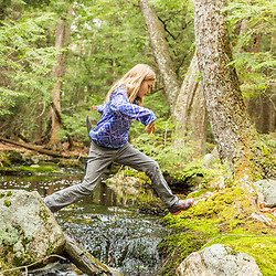 A girl crosses a small stream in the Stonehouse Forest in Barrington, New Hampshire.