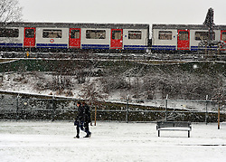 CORRECTION: DISTRICT LINE TRAIN NOT PICCADILLY AS PREVIOUSLY STATED © Licensed to London News Pictures. 18/01/2013. London, UK A couple walk through a park as a District Line tube train passes by in the snow. Snow in West London today 18th January 2013. Photo credit : Stephen Simpson/LNP
