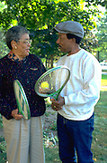 Friends age 70 discussing tennis swing in the park.  St Paul  Minnesota USA