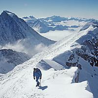 MOUNTAINEERING. Mike McDowell on summit ridge of 4650-meter Mount Shinn, Antarctica's third highest summit. 4,852-meter Mount Tyree (Antarctica's second highest peak) in background.  Ellsworth Mountains.