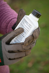 Reading the safety instructions on a bottle of weedkiller