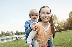 Brother and sister having fun together in a park, Munich, Bavaria, Germany