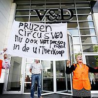 """Nederland, Amsterdam Z.O. , 13 augustus 2013.<br /> Overhandiging petitie werknemers distributiecentrum Aduard aan directie V&D.<br />  Ca. 50 werknemers van V&D distributiecentrum Aduard (Groningen), enkele werknemers van V&D-filialen, Toon Wennekers, coördinator arbeidsvoorwaardenbeleid FNV Bondgenoten en FNV Bondgenoten <br /> Overhandiging petitie en veren aan de V&D-directie voor fatsoenlijk sociaal plan. Werknemers V&D willen een goed sociaal plan, geen veren Circa 50 werknemers van het V&D-distributiecentrum in Aduard reizen dinsdagochtend naar Amsterdam waar zij rond 11.00 uur een petitie voor een fatsoenlijk sociaal plan aan de V&D-directie overhandigen. Het ultimatum dat zij V&D stelden, liep maandagmiddag af zonder enige handreiking van V&D. Toon Wennekers, coördinator arbeidsvoorwaardenbeleid bij FNV Bondgenoten, steunt de werknemers en is bij de overhandiging aanwezig. """"We willen geen veren, we willen een fatsoenlijke ontslagvergoeding"""" """"Jarenlang kregen we veren in onze kont gestoken maar nu V&D van ons af wil, worden we met een fooitje afgescheept"""", aldus een werknemer<br /> Foto:Jean-Pierre Jans"""