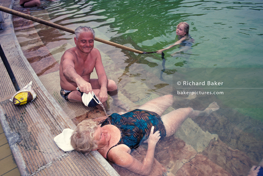 A middle-age husband pours thermal healing spa waters on to his wife in Budapest's famous Szechenyi thermal bath, on 18th June 1990, in Budapest, Hungary. Budapest is especially known for its spas. The Széchenyi Medicinal Bath  (Szechenyi-gyogyfurdo) is the largest medicinal bath in Europe. Its water is supplied by two thermal springs, their temperature is 74°C/165°F and 77°C/171°F, respectively. The bath can be found in the City Park, and was built in 1913 in Neo-baroque style to the design of Gyozo Czigler.