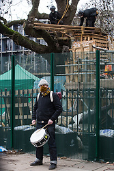 London, UK. 31 January, 2021. A samba drummer performs in front of climbers from the National Eviction Team (NET) dismantling a camp in Euston Square Gardens built by anti-HS2 activists from umbrella campaign group HS2 Rebellion seeking to protect trees there from felling by HS2 Ltd in connection with the controversial HS2 high-speed rail project. Five activists continue to occupy tunnels beneath the camp, including Dan Hooper who was known as the roads protester Swampy during the 1990s.