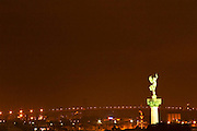 A view over the rooftops and city of Bordeaux with the Pont d'Aquitaine over the Garonne river at night. The statue 'La Liberte brisant ses fers' (Liberty breaking her chains)