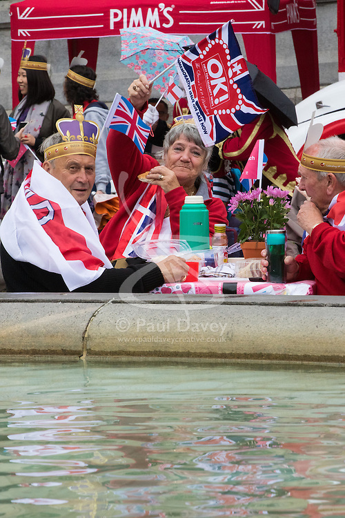 Trafalgar Square, London, June 12th 2016. Rain greets Londoners and visitors to the capital's Trafalgar Square as the Mayor hosts a Patron's Lunch in celebration of The Queen's 90th birthday. PICTURED: A group from Nottingham ignore the rain as they enjoy the atmosphere in Trafalgar Square.