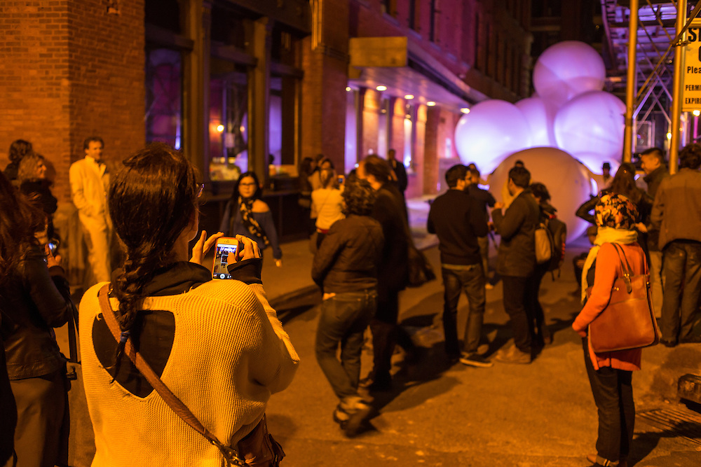 A crowd looks down Jersey Street at a pile of inflated balls, part of a performance by Snarkitecture.