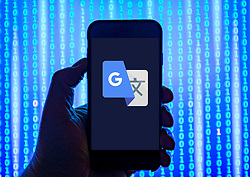 Person holding smart phone with Google Translate   logo displayed on the screen. EDITORIAL USE ONLY