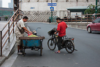 street seller with fruit and customer on moped in Shanghai China