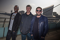 © Licensed to London News Pictures . 19/03/2015 . Salford Quays , UK . Paul Leveridge ( Kermit ) , Mark Berry ( Bez ) and Shaun Ryder at Salford Quays . Black Grape photocall at The Green , Salford Quays , Greater Manchester . Black Grape are reforming for a Madchester charity gig along with other local bands , to raise awareness for Bez's Reality Party and anti-fracking . Photo credit : Joel Goodman/LNP