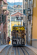 Funicular - Elevador da Bica - with graffiti carrying local people and tourists climbs steep hill in City of Lisbon, Portugal