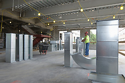 Central Connecticut State University.  New Academic Building.  Project No: BI-RC-324 Contractor: Gilbane Building Company, Glastonbury, CT. Date of Photograph: 19 June 2012 Image No. 61 Camera View: Worker Inspecting HVAC Ducting in Position to Install.