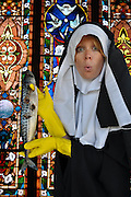"""Humorous photograph of a nun in church holding a Norwegian Mackerel with holes in it visually depicting the saying """"Holy mackerel!"""""""