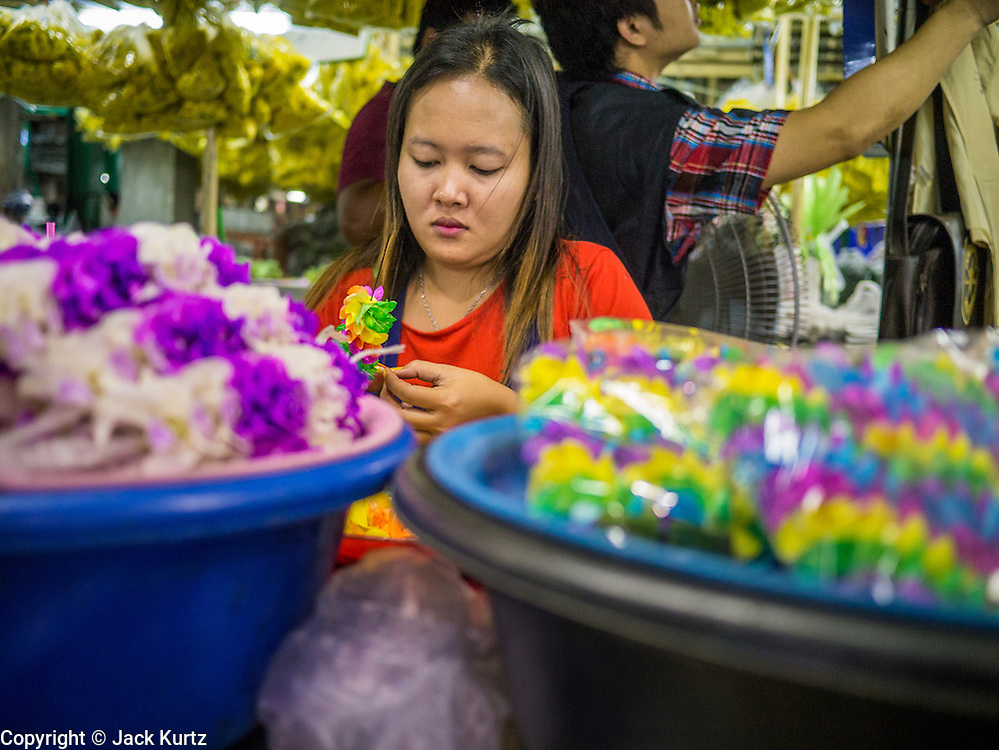 19 OCTOBER 2012 - BANGKOK, THAILAND:   A vendor makes flower garlands in the Bangkok Flower Market. The Bangkok Flower Market (Pak Klong Talad) is the biggest wholesale and retail fresh flower market in Bangkok.  The market is busiest between 3:30AM and 6AM. Thais grow and use a lot of flowers. Some, like marigolds and lotus, are used for religious purposes. Others are purely ornamental.         PHOTO BY JACK KURTZ