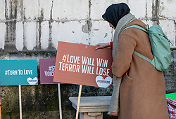 © Licensed to London News Pictures. 02/12/2019. London, UK. A Women arranges posters at the Vigil at the Guildhall London for the victims of the London Bridge attack on Friday 29/11/2019. Photo credit: Alex Lentati/LNP