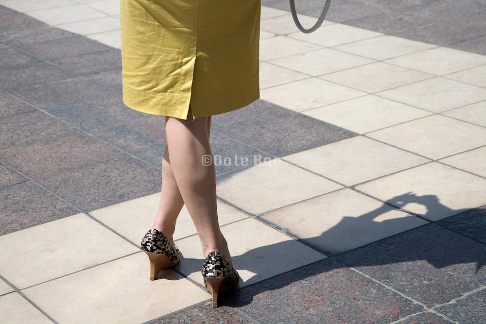 fashionable dressed woman standing cross legged