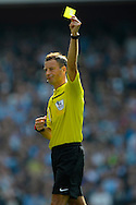 Referee Mark Clattenburg gives a yellow card to Arsenal's Nacho Monreal . Barclays Premier league match, Arsenal v Manchester city at the Emirates Stadium in London on Saturday 13th Sept 2014.<br /> pic by John Patrick Fletcher, Andrew Orchard sports photography.