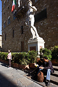 "With tourists below, the replica of Michelangelo's David statue stands beneath Palazzo Vecchio in Florence's Piazza della Signoria. It is said that the genitals were created smaller to imply that David was not allowing himself to make decisions with pleasure in mind. ""David"" is a masterpiece of Renaissance sculpture created between 1501 and 1504, by the Italian artist Michelangelo. It is a 5.17 metre (17 feet) marble statue of a standing male nude. The statue represents the Biblical hero David, a favoured subject in the art of Florence but soon came to symbolise the defence of civil liberties in the Florentine Republic, an independent city-state threatened on all sides by more powerful rival states and by the Medici family."