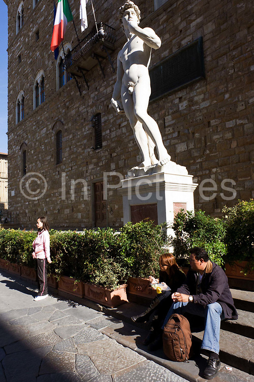 """With tourists below, the replica of Michelangelo's David statue stands beneath Palazzo Vecchio in Florence's Piazza della Signoria. It is said that the genitals were created smaller to imply that David was not allowing himself to make decisions with pleasure in mind. """"David"""" is a masterpiece of Renaissance sculpture created between 1501 and 1504, by the Italian artist Michelangelo. It is a 5.17 metre (17 feet) marble statue of a standing male nude. The statue represents the Biblical hero David, a favoured subject in the art of Florence but soon came to symbolise the defence of civil liberties in the Florentine Republic, an independent city-state threatened on all sides by more powerful rival states and by the Medici family."""