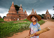 A young boy and his bamboo musical instrament in front of a temple and stupas in Bagan, Myanmar.