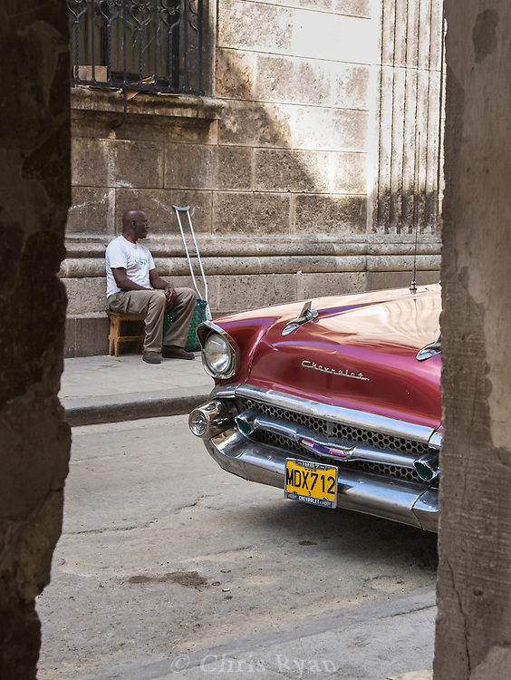 Man on street behind old Chevrolet seen through doorway, Havana, Cuba