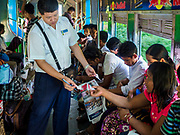 25 NOVEMBER 2017 - YANGON, MYANMAR: A conductor checks tickets on the Yangon Circular Train. The Yangon Circular Train is a 45.9-kilometre (28.5 mi) 39-station two track loop system connects satellite towns and suburban areas to downtown. The train was built during the British colonial period, the second track was built in 1954. Trains currently run both directions (clockwise and counter-clockwise) around the city. The trains are the least expensive way to get across Yangon and they are very popular with Yangon's working class. About 100,000 people ride the train every day. A a ticket costs 200 Kyat (about .17¢ US) for the entire 28.5 mile loop.    PHOTO BY JACK KURTZ